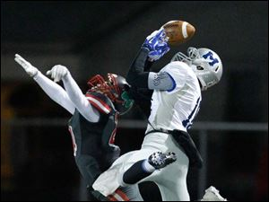 Toledo Central Catholic player Derich Weiland, 24, breaks up a pass intended for Grafton Midview player Eric Lauer, 10, during the first quarter of their Division II playoff game at Gallagher Stadium in Toledo.
