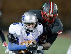 Toledo Central Catholic player Keith Towbridge, 89, sacks Grafton Midview quarterback Cody Callaway, 8, to end the first quarter of their Division II playoff game at Gallagher Stadium in Toledo.