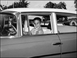 This 1957 photo shows 10-year-old Mitt Romney in Detroit behind the wheel of a Nash automobile, manufactured by American Motors Corp.
