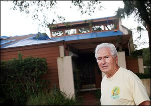 Richard Campanaro stands in front of an empty townshome in Cranes Roost Villas in Altamonte Springs, Fla. Mr. Campanaro says the home is a foreclosure that Bank of America has allowed to fall into disrepair. By slowly releasing their properties, some lenders can benefit from rising home values.