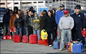 People line up at a gas station waiting to fill up in Newark, N.J. In parts of New York and New Jersey, drivers lined up for hours at gas stations that were struggling to stay supplied.