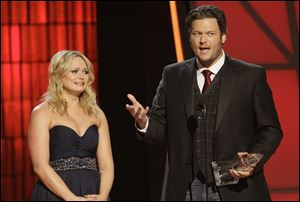 "Miranda Lambert, left, and Blake Shelton accept song of the year award for ""Over You"" at the 46th Annual Country Music Awards at the Bridgestone Arena on Thursday in Nashville, Tenn. Lambert got emotional as Shelton talked about the loss of his brother Richie and the song he wrote to honor him."