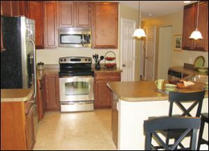 The efficient kitchen includes a peninsula snack bar, open to the great room.