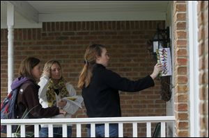Woodland Elementary School kindergarden teacher Olivia Zuchowski, right, leaves a pamphlet of information on the proposed school levy Saturday morning while canvasing with two other teachers in Perrysburg. Several volunteers were on hand to knock on doors and ask residents whether or not they planned on supporting the school levy in the upcoming November election.