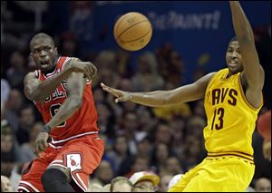 Chicago Bulls' Luol Deng saves the ball from going out of bounds, next to Cleveland Cavaliers' Tristan Thompson in the third quarter tonight in Cleveland.