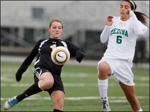 Perrysburg's Lucy Walton (4) kicks the ball against  Medina's Lilly  Jackson (6).