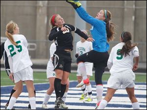 Perrysburg's Mollie Whitacre (20)  takes a shot against Medina goalie Jordan Reynolds (0).