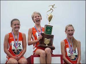 Liberty Center High School runners Brittany Atkinson, eft, Kelly Haubert, center, and Paige Chamberlain celebrate winning their title.