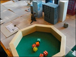 Dice, buildings and Godzilla-like characters make up the gaming board of