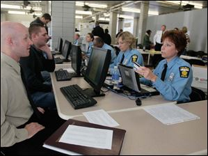 Jourdan Rupert, of Genoa, left, puts in an application to Toledo Police officer Chris Holland, right.