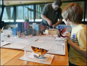 Mothra sits near a gaming board while players move other Godzilla-like characters in a game called