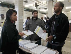 City of Toledo human resources employee Erica Powell, left, speaking with Glenn Carter, center, and Michael Hatchett, both of Detroit, about the city's exam.