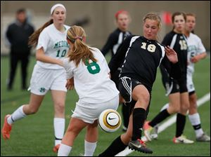 Perrysburg's Allex Brown (18) moves the ball against Medina's Leanne Prandi (8).