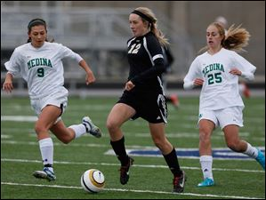 Perrysburg's Maddy Williams (12) moves the ball against  Medina's Holly Rhodes (9) and Brianna Caccavale (25).