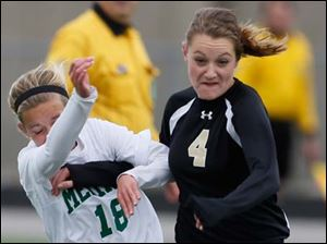Perrysburg's Lucy Walton (4) kicks the ball against  Medina's Sydney Leckie (18).