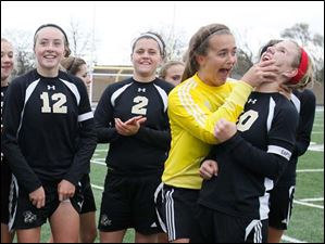 Perrysburg's Maddy Williams (12), Sam Schrader (2), Chloe Buehler, and Mollie Whitacre (20) celebrate defeating Medina.