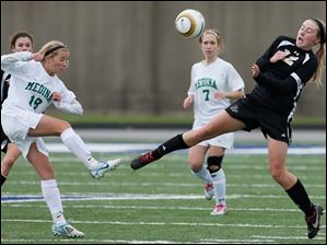 Perrysburg's Maddy Williams (12) battles for possession with Medina's Sydney Leckie.