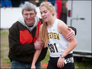Sylvania Northview runner Robin Foster is helped by a race volunteer after finishing.