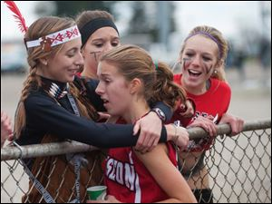 Wauseon High School runner Taylor Vernot is greeted by her teammates, Megan Beck and Mickenna Schweinhagen, rear, after Vernot took fourth in the race.