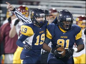 Whitmer's Marquise Moore, 91, comes up with a fumble recovery with teammate Tylor Schneider.