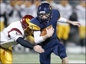 Whitmer quarterback Nick Holley slips past Avon Lake's Matt Russell.