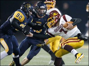 Whitmer players Marquise Moore, 90, and Nathan Holley, 18, sack Avon Lake quarterback David Winkel.