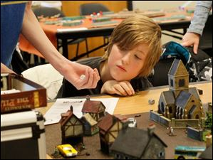 Henry Brown, 11, of Perrysburg, watches his brother Nathan, 13, roll the dice while playing