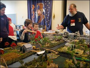 Game master John Patrick leads a few young gamers through
