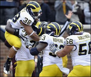Michigan's A.J. Williams, second from left second, hoists running back Thomas Rawls (38) after Rawls scored a touchdown against Minnesota during the second quarter of an NCAA college football game, Saturday, in Minneapolis. Michigan's Stephen Hopkins (33) and Joey Burzynski (56) join the celebration.