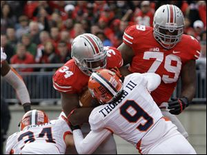 Ohio State running back Carlos Hyde (34) scores a touchdown as teammate Marcus Hall, right, tries to block Illinois defenders Mike Svetina, left, and Earnest Thomas. Hyde rushed for 139 yards and three TDs.