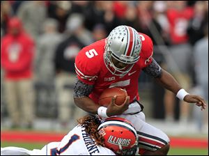 Ohio State quarterback Braxton Miller is tackled by Illinois defensive back Terry Hawthorne.