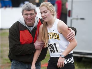 Sylvania Northview runner Robin Foster is helped by a race volunteer after finishing the Girls Div. I State High School Cross Country Championship, at National Trail Raceway in Hebron, Ohio.