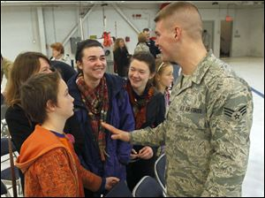 Toledoan Senior Airman Sean Fitzpatrick meets with his family after being honored during the Hometown Heroes Salute ceremony at the 180th Fighter Wing in Swanton.