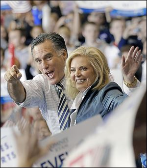 GOP presidential candidate Mitt Romney and his wife, Ann, greet about 6,000 in Cleveland. He outlined Sunday his first official acts should he win on Tuesday.