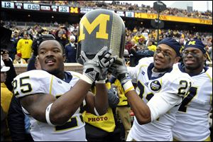 "From left, Michigan's Kenny Demens, Roy Roundtree and Brandin Hawthorne carry the ""Little Brown Jug"" off the field after defeating Minnesota 35-13 Saturday in Minneapolis."