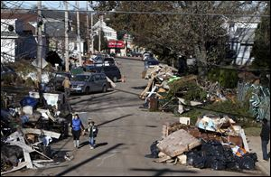 Garbage lies piled on the street in the New Dorp neighborhood of Staten Island, N.Y., on Sunday. FEMA says 182,000 individuals in Connecticut, New York, and New Jersey have registered for aid.