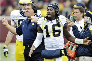 Michigan head coach Brady Hoke, left, and quarterback Denard Robinson, right, need to end the season strong and hope Nebraska stumbles to win the Legends Division.