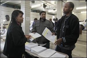 Erica Powell, left, a city of Toledo human resources employee, speaks with Glenn Carter, center, and Michael Hatchett, both of Detroit, at the Michael P. Bell Fire Administration Building about the application process.
