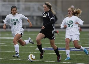 Perrysburg's Maddy Williams moves the ball against  Medina's Holly Rhodes (9) and Brianna Caccavale (25) during the Division II regional soccer final Saturday in Sandusky, Ohio.