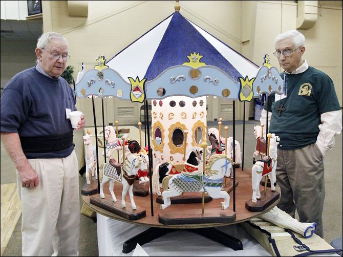 Norville Cramer of Hillsdale, Mich., left, views wooden horses and a rotating carousel made by Don Brewer of Toledo's Old West End, right, during an exhibit of works by the Black Swamp Woodcarvers at the St. Clement Community Center in Toledo. Members of the woodcarvers club range from beginners to those with many years of experience, and the exhibit Sunday displayed a variety of wood-carving techniques.