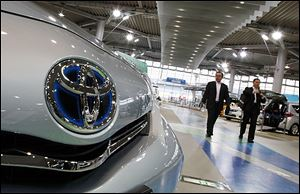 A couple walk by Lexus models displayed at a Toyota Motor Corp. showroom in Tokyo. Toyota's quarterly profit tripled, driven by a recovery from natural disasters, and the company raised its full-year earnings forecast despite a sales slump in China.