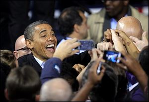 President Barack Obama smiles for cameras as he shakes hands with supporters after speaking at a campaign event at Nationwide Arena Monday, Nov. 5, 2012, in Columbus, Ohio.