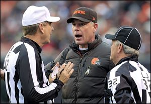 Cleveland Browns head coach Pat Shurmur, center, argues a call with referee Jeff Triplette, left, and line judge Jeff Bergman in the first quarter of an NFL football game against the Baltimore Ravens, Sunday, Nov. 4, 2012, in Cleveland. (AP Photo/Tony Dejak)