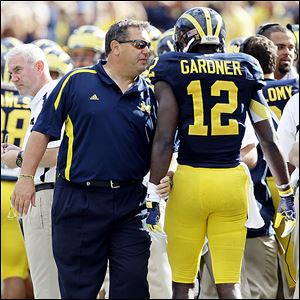 Michigan football coach Brady Hoke, left, hasn't experienced bad timing or bad karma during his time in Ann Arbor, unlike his predecessor, Rich Rodriguez.