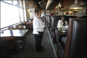 Lisa Schnabel, left, finishes up serving a table for customer Robin Reid, right, at the Admiral's American Grill.