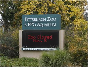 An electronic display sign near the entrance for the Pittsburgh Zoo and PPG Aquarium shows the zoo is closed on today in Pittsburgh. Zoo officials said a young boy was killed after he fell into the exhibit that was home to a pack of African painted dogs who pounced on the boy and mauled him on Sunday.