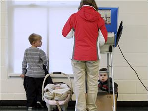 Kim Helms, with her children, son Ethan, 7, left, Annabel, 2 months old, in carrier, and son Isaac, 3, behind voting machine, casts her ballot at Fort Meigs Elementary School in Perrysburg.