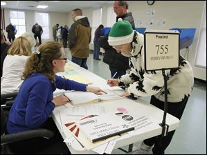 Poll worker Elizabeth Emmert, left, shows Eleanor Simon where to sign, before she casts her ballot at  Fort Meigs School.  Eleanor's husband, Terry Simon, behind her.