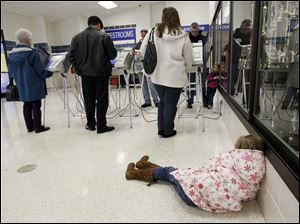 Sarah Vandergrift, 7, rests on the floor as her mother, Emily Vandergrift, votes at Springfield High School.