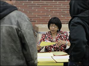 Poll worker Francine Nash helps voters cast provisonal ballots at the Kent Branch of the Toledo-Lucas County Public Library.